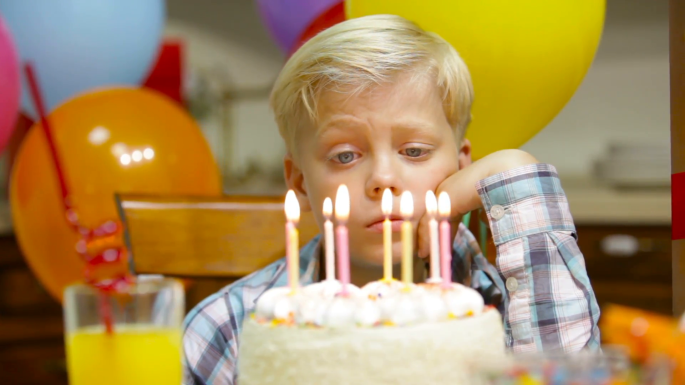 sad-little-boy-celebrating-his-birthday-alone-suddenly-cheering-up-and-blowing-the-candles_4kxwwj8wg__F0000